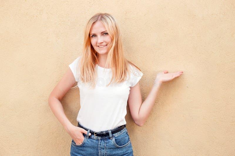 Menina do moderno que veste o t-shirt vazio e as calças de brim brancos que levantam contra a parede áspera da rua, estilo urbano fotografia de stock royalty free