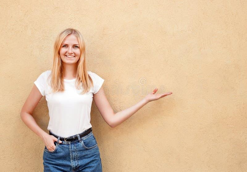 Menina do moderno que veste o t-shirt vazio e as calças de brim brancos que levantam contra a parede áspera da rua, estilo urbano imagens de stock royalty free