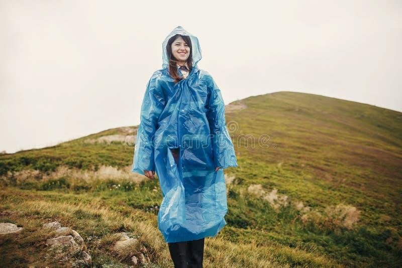 Menina do moderno do viajante que sorri na capa de chuva azul com a trouxa, ex imagem de stock royalty free