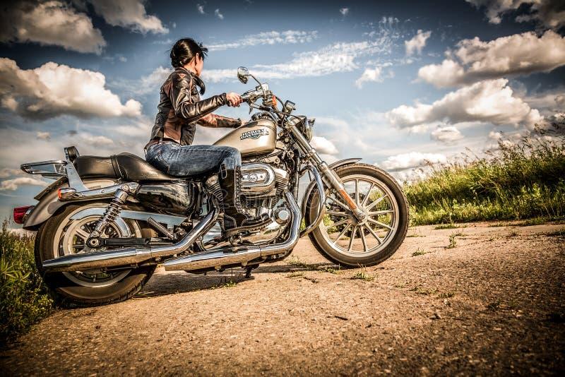 Menina do motociclista e bicicleta Harley Sportster imagens de stock royalty free