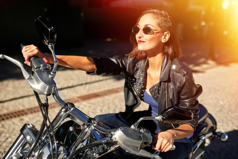 Menina do motociclista em um casaco de cabedal que monta uma motocicleta foto de stock