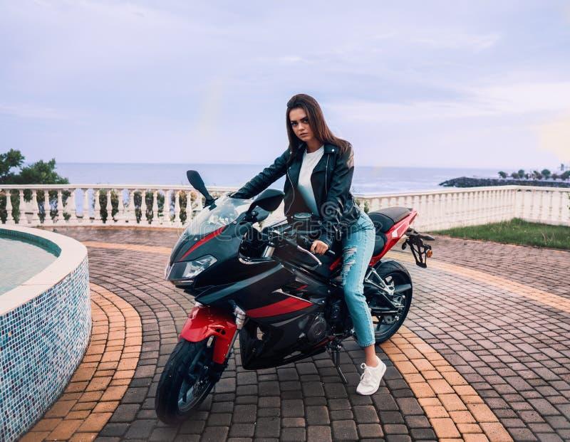Menina do motociclista em um casaco de cabedal em uma motocicleta da cor preta e vermelha imagens de stock