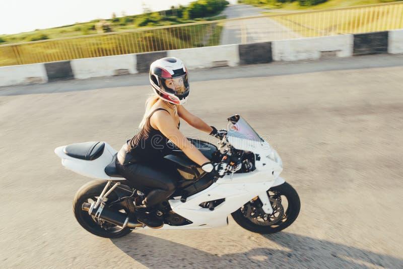 A menina do motociclista em um couro veste-se em uma motocicleta imagem de stock royalty free