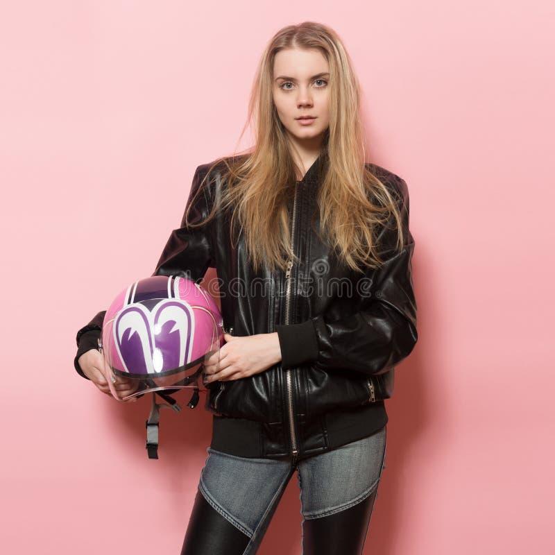 Menina do motociclista que veste o casaco de cabedal preto que guarda o capacete cor-de-rosa da motocicleta imagem de stock
