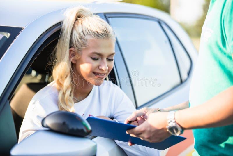 Menina do motorista do principiantes em um teste de condução com seu instrutor fotos de stock royalty free