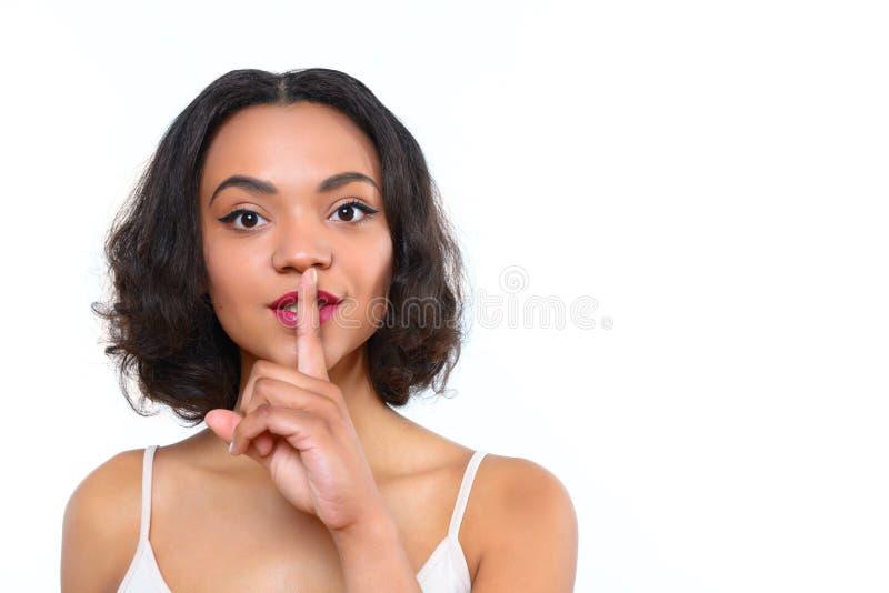 Menina do mulato com o indicador em sua boca fotos de stock