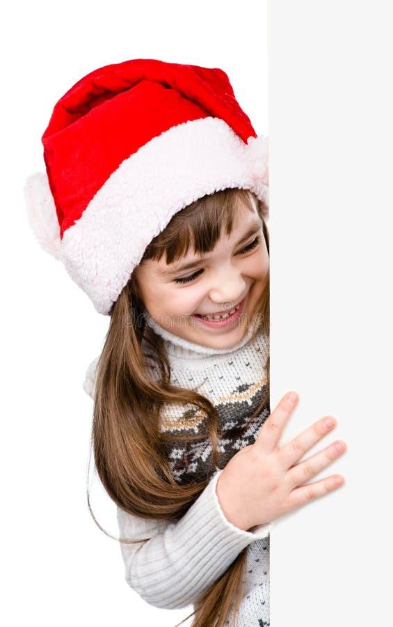 Menina do Natal no chapéu do ajudante de Santa com placa branca vazia isola fotografia de stock royalty free
