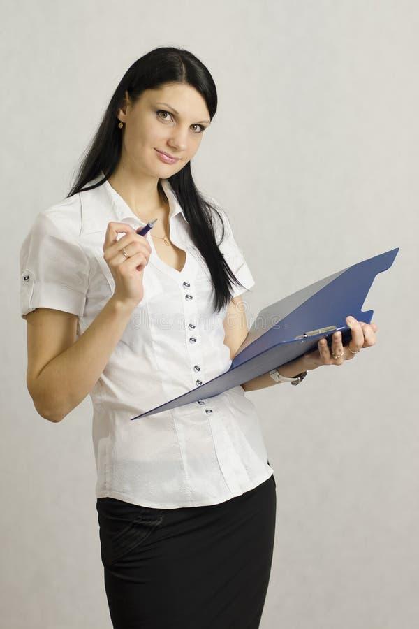 A menina do negócio escuta e faz anotações em um dobrador imagem de stock