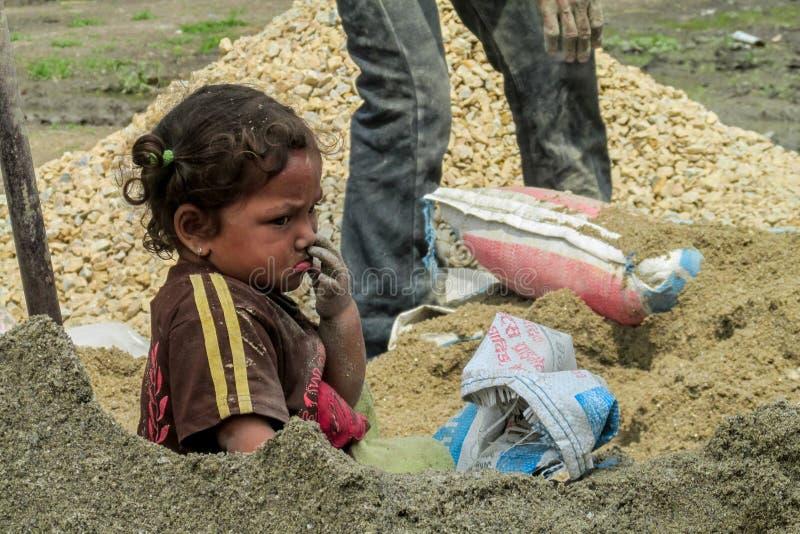 Menina do Nepali que senta-se em pedras na roupa suja imagem de stock royalty free