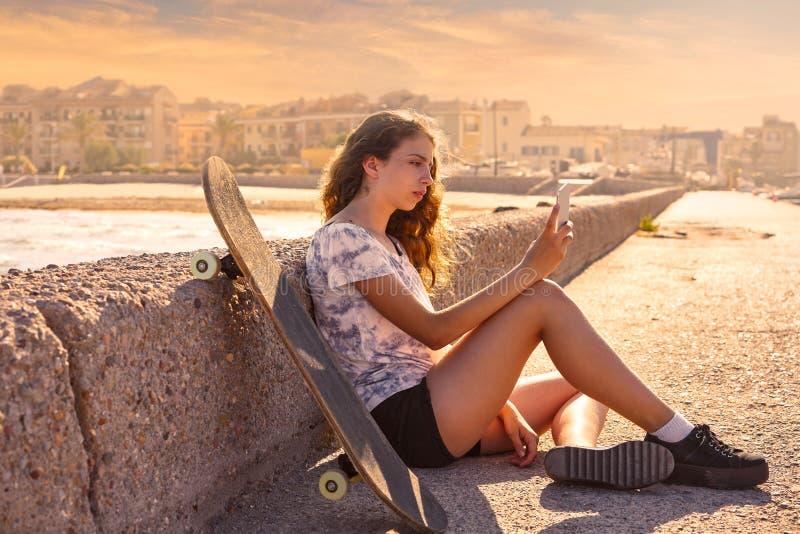 Menina do patim de rolo com assento do smartphone fotografia de stock royalty free