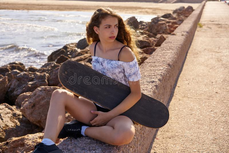 Menina do patim de rolo em uma doca da praia com vermelho foto de stock