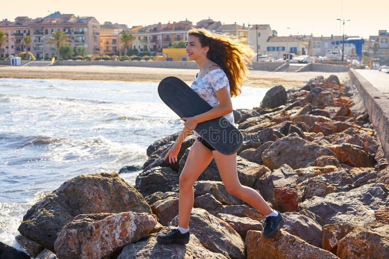 Menina do patim de rolo em uma doca da praia com vermelho imagem de stock
