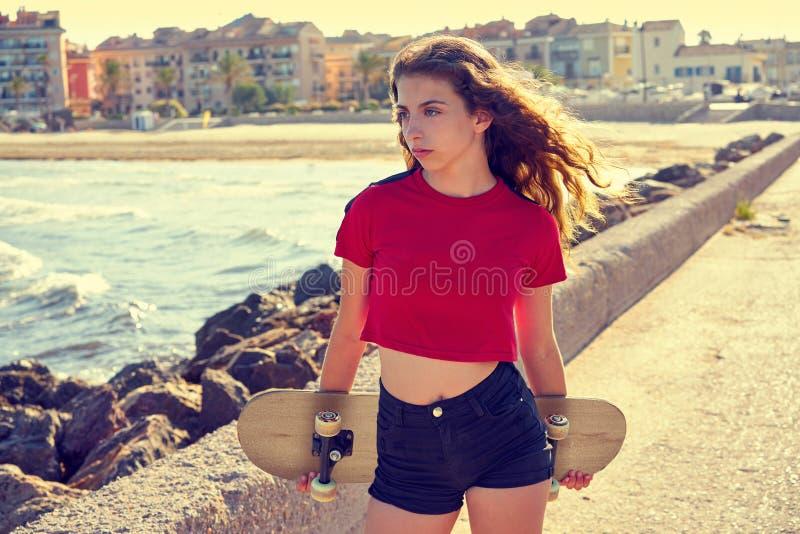 Menina do patim de rolo em uma doca da praia com vermelho foto de stock royalty free