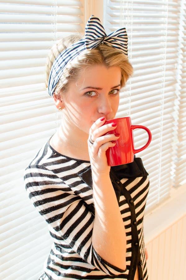A menina do Pinup com bordos vermelhos prega o café ou o chá bebendo que guardam o copo vermelho & que olham a câmera sobre as co fotografia de stock