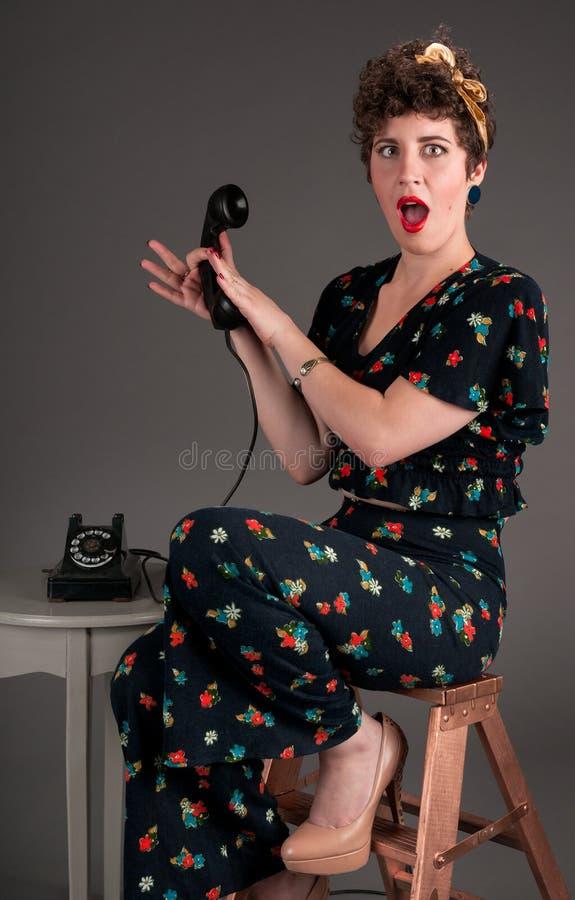 Menina do Pinup no equipamento florescido chocado pela informação do telefone imagens de stock royalty free