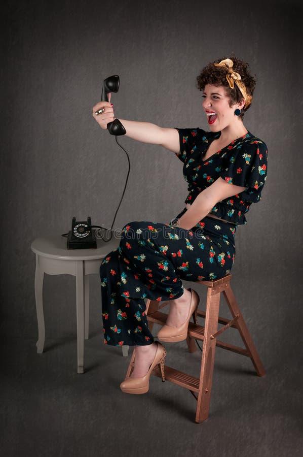 Menina do Pinup no equipamento florescido entusiasmado com informação do telefone fotografia de stock