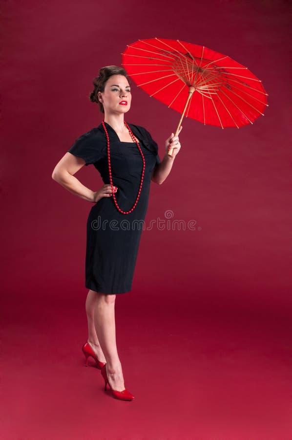 Menina do Pinup no vestido preto altivo com parasol vermelho imagem de stock