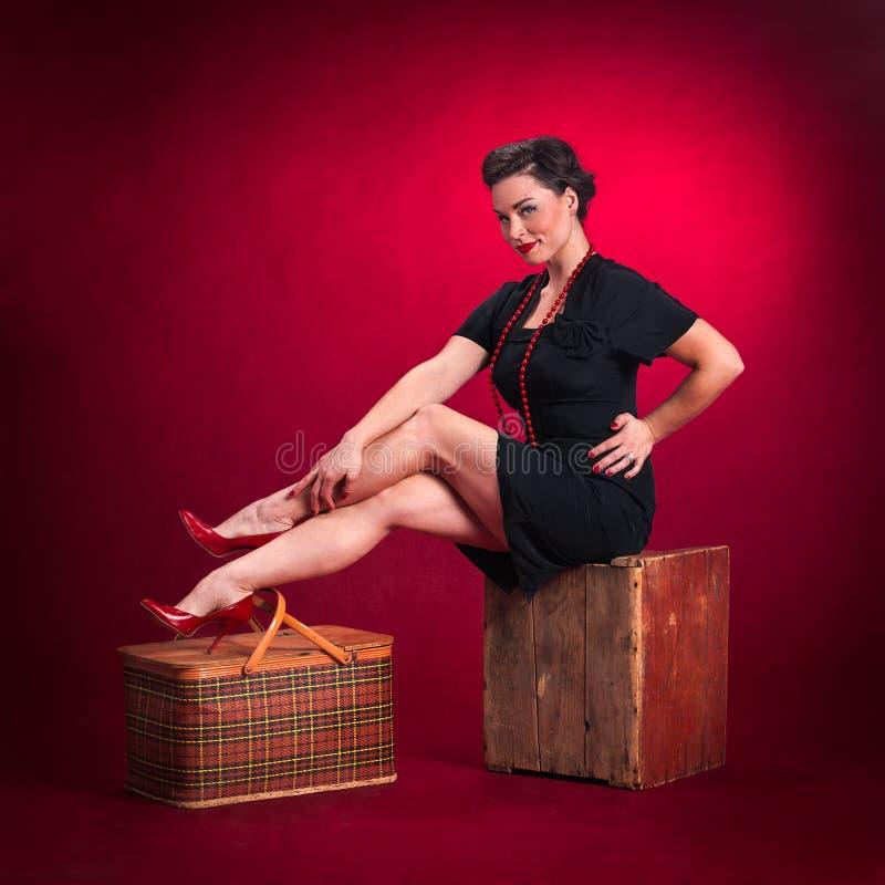 A menina do Pinup no vestido preto senta-se na caixa de madeira foto de stock royalty free