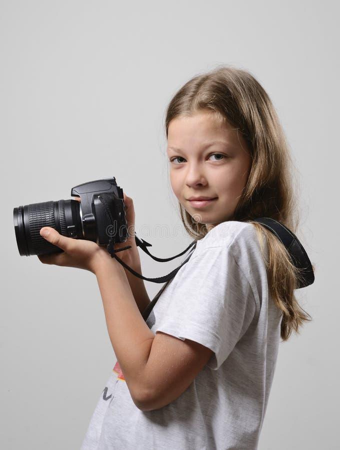 Menina do Preteen com a câmera do slr fotografia de stock royalty free