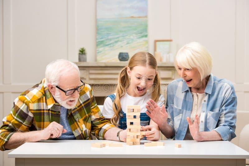 Menina do Preteen com o avô e a avó que jogam o jogo do jenga em casa imagens de stock