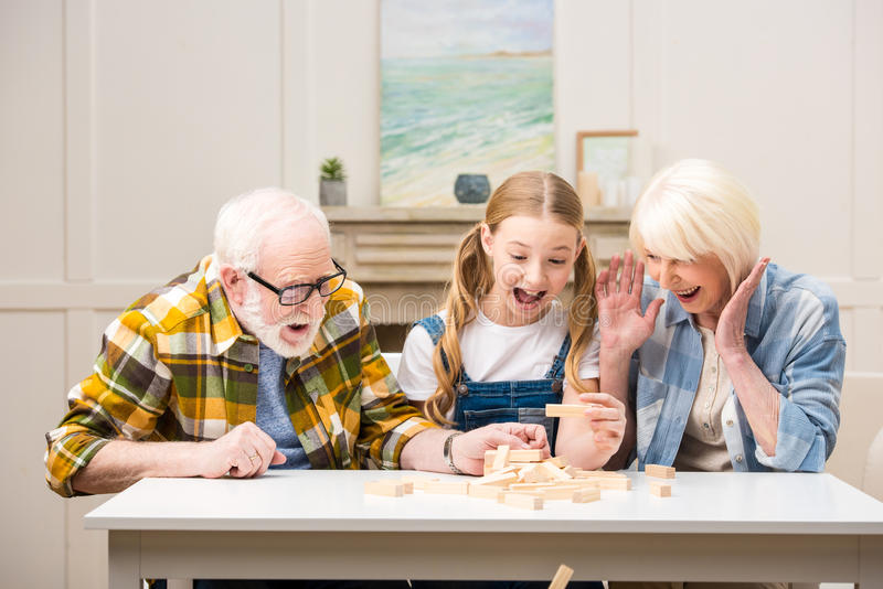 Menina do Preteen com o avô e a avó que jogam o jogo do jenga em casa imagem de stock royalty free