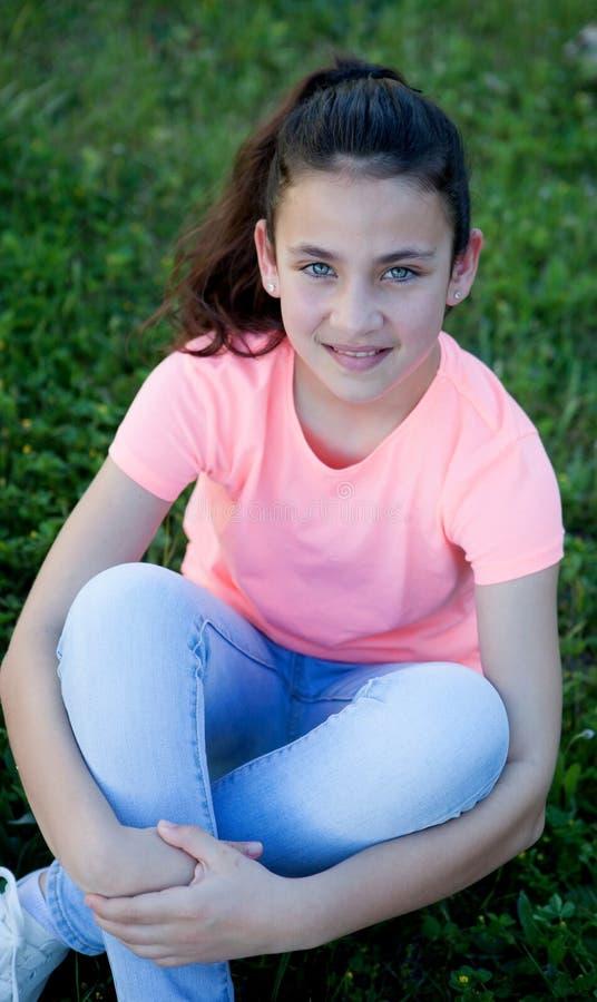 Menina do Preteen com os olhos azuis que sentam-se na grama imagens de stock