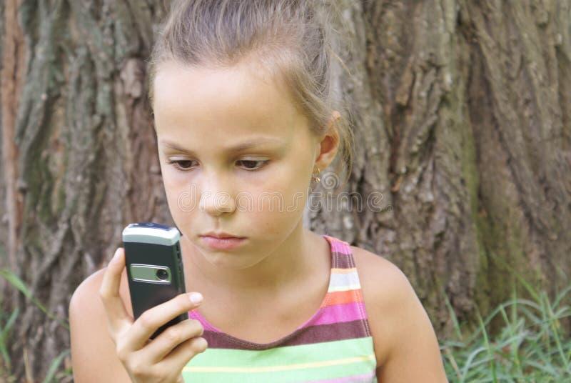 Menina do Preteen com telefone de pilha fotos de stock royalty free
