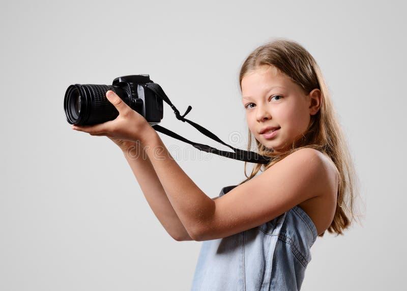 Menina do Preteen com uma câmera grande fotografia de stock