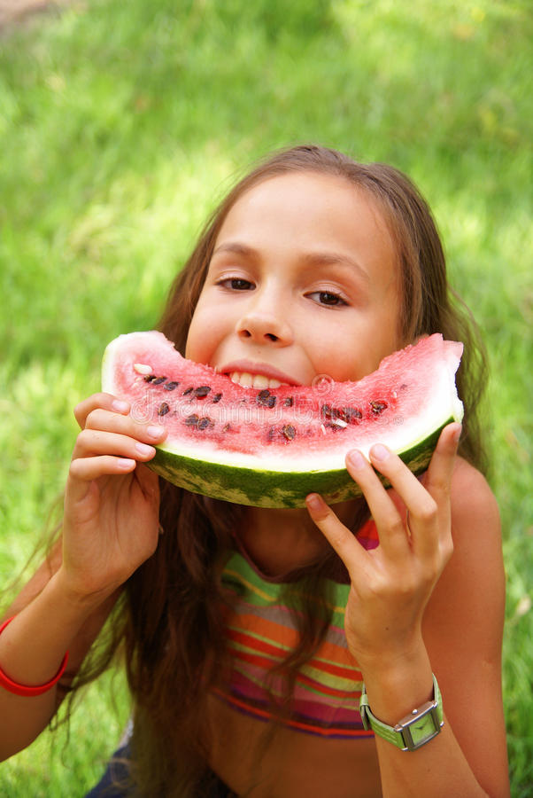 A menina do Preteen come o watermellon foto de stock royalty free