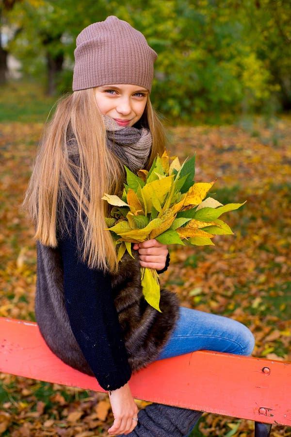 Menina do Preteen no parque do outono com folhas fotos de stock
