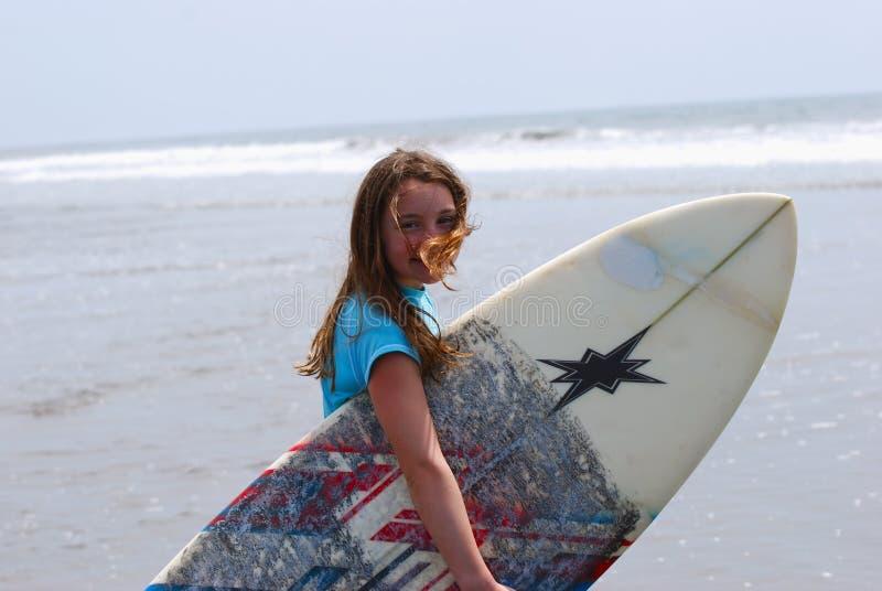 Menina do Preteen que carreg uma prancha ao oceano imagens de stock royalty free