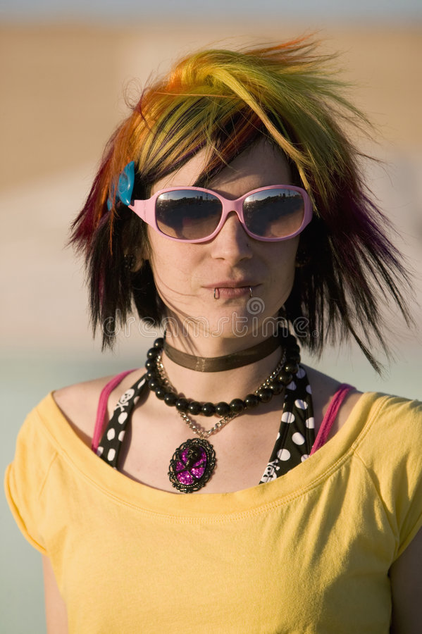 Menina do punk com os óculos de sol coloridos e grandes brilhantes fotografia de stock royalty free
