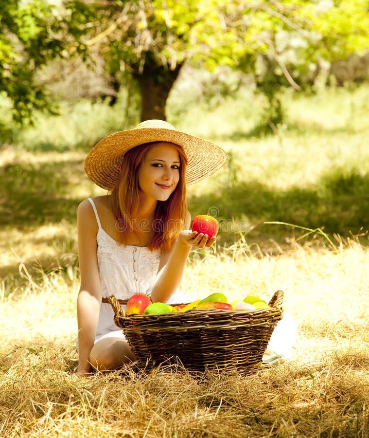 Menina do Redhead com fruta no jardim. fotografia de stock royalty free