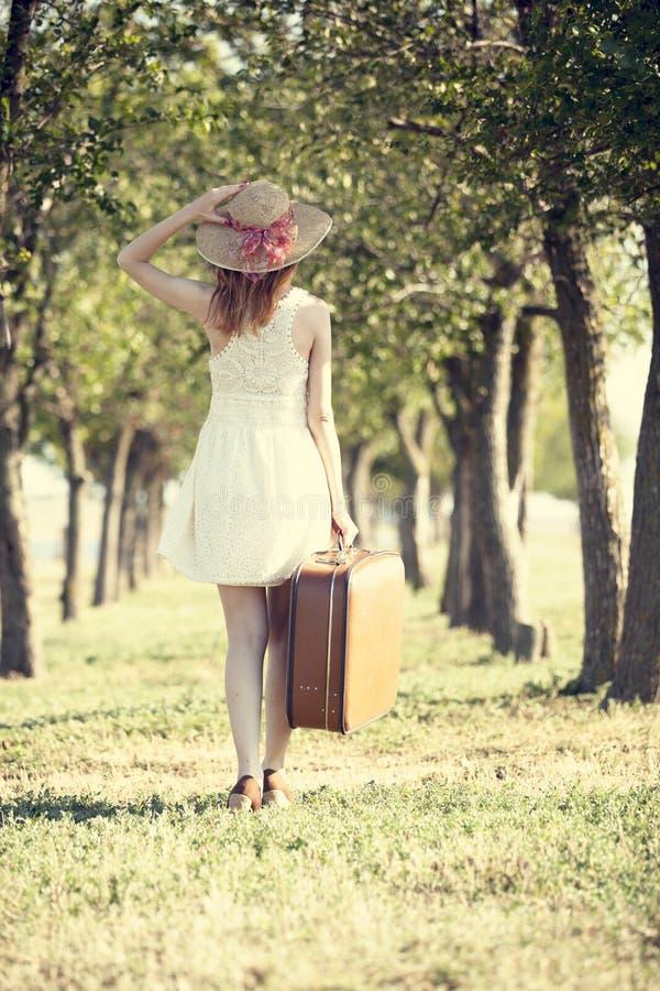 Menina do Redhead com a mala de viagem na aléia da árvore. foto de stock