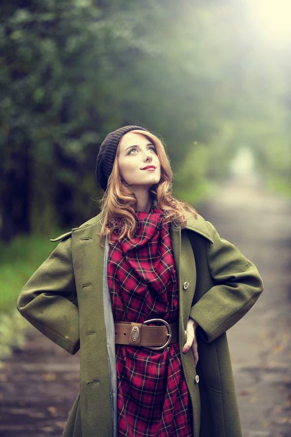 Menina do redhead do estilo na aléia bonita do outono. imagens de stock