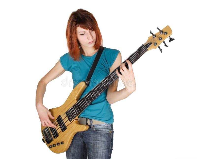 Menina do Redhead que joga a guitarra baixa, meio corpo fotos de stock royalty free