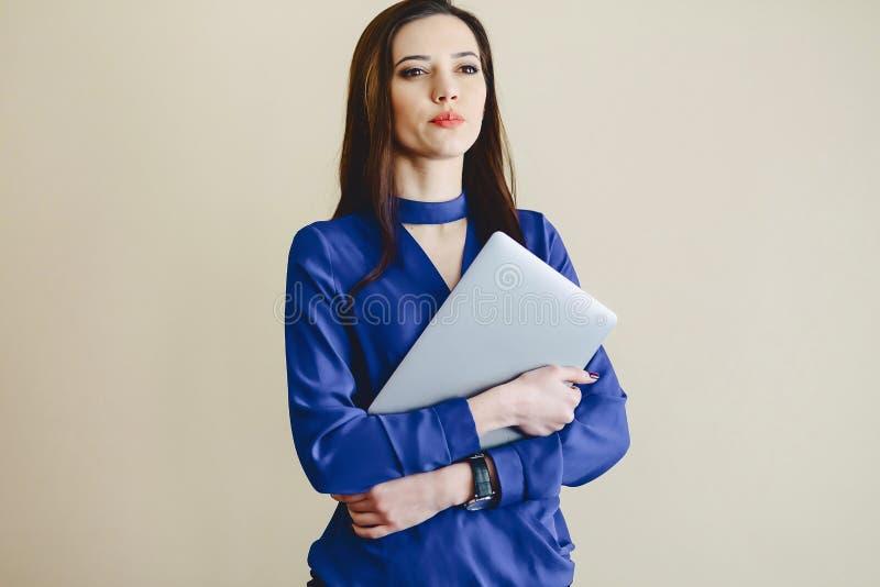 menina do retrato com o portátil no fundo da parede fotografia de stock royalty free