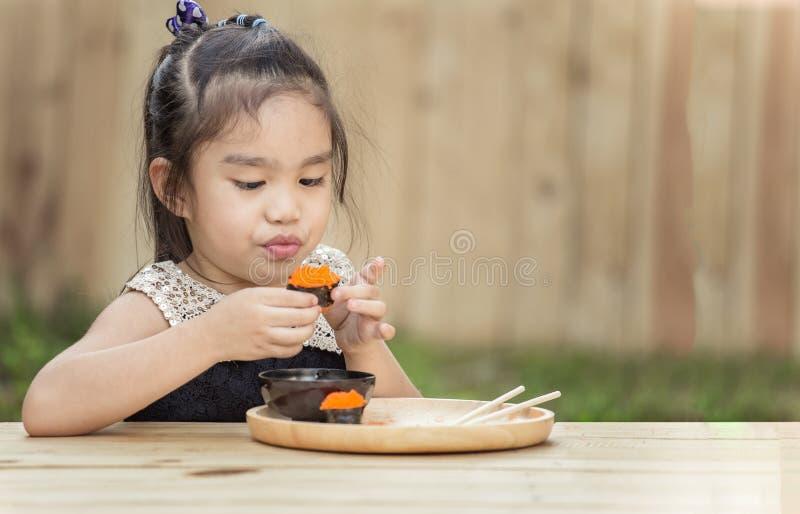 Menina do retrato que come o sushi imagens de stock royalty free