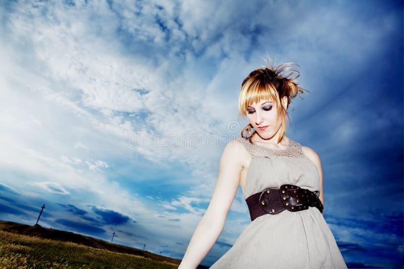 Menina do retrato que veste fora o vestido com céu azul fotografia de stock royalty free