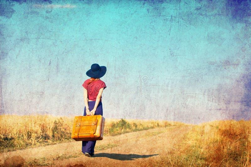 Menina do ruivo com a mala de viagem na estrada do campo fotos de stock royalty free