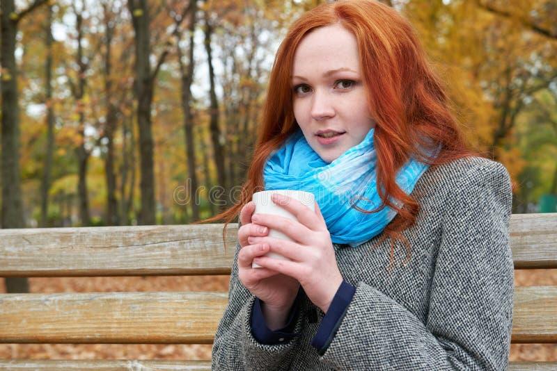 A menina do ruivo com o copo do chá senta-se em um banco no parque da cidade, outono fotografia de stock
