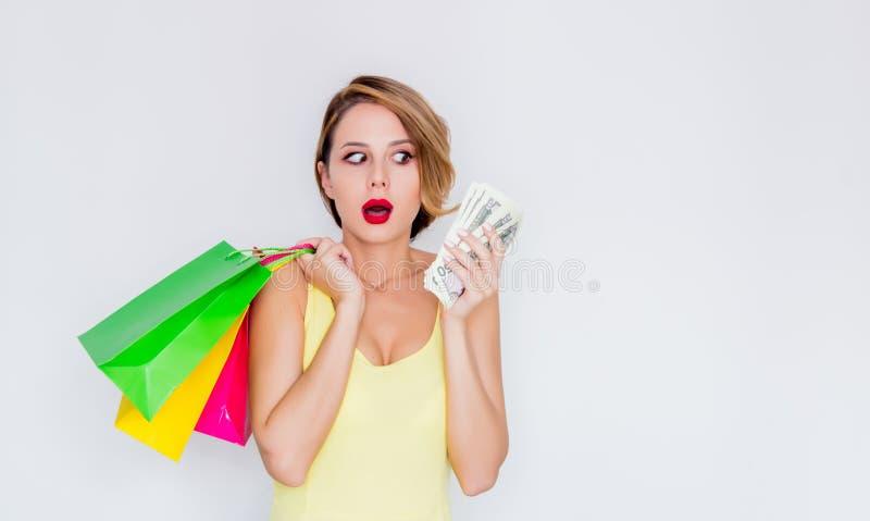 Menina do ruivo com sacos de compras e dinheiro imagem de stock