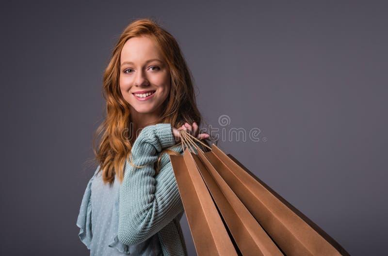 Menina do ruivo com sacos de compras imagem de stock