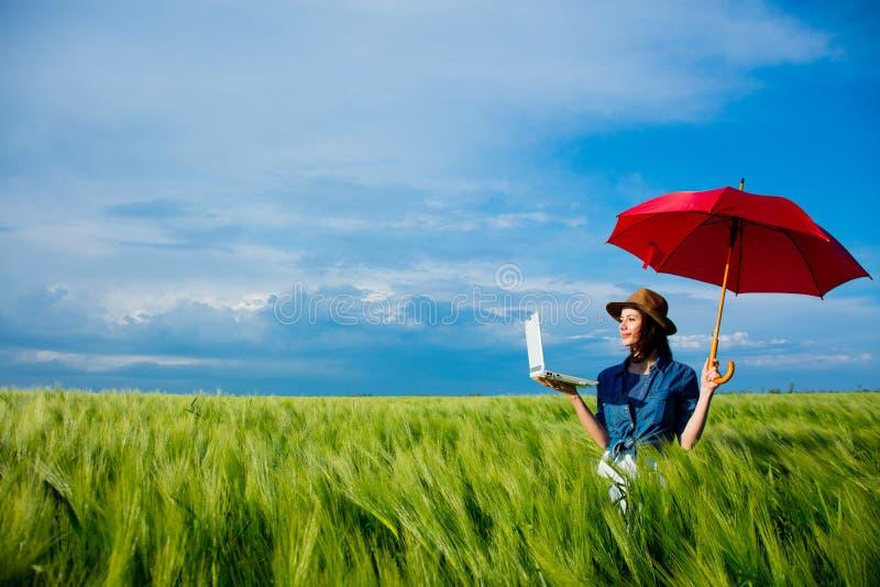 Menina do ruivo de Beautfiul com portátil e guarda-chuva imagens de stock royalty free