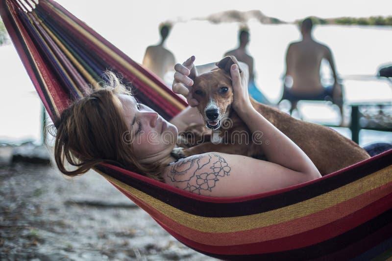 Menina do ruivo e seu cão que encontram-se em uma sala de estar na praia no verão imagem de stock royalty free