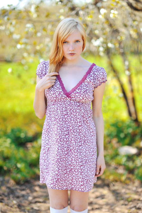 Menina do ruivo no jardim de florescência da mola fotos de stock royalty free