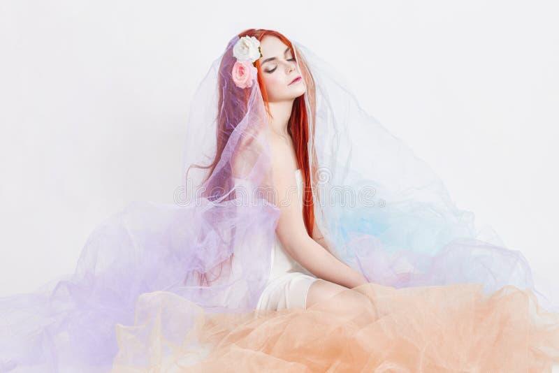 A menina do ruivo no vestido colorido pairoso leve senta-se no fundo do branco do assoalho Flores bonitas no cabelo da menina Mul imagens de stock royalty free