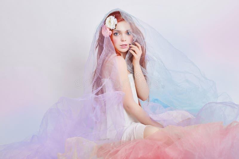 A menina do ruivo no vestido colorido pairoso leve senta-se no fundo do branco do assoalho Flores bonitas no cabelo da menina Mul fotografia de stock royalty free