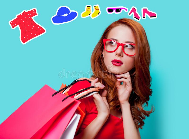 Menina do ruivo nos monóculos com sacos de compras fotografia de stock royalty free