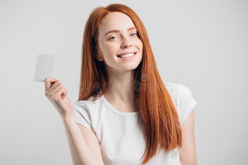 Menina do ruivo que guarda o cartão de crédito e que sorri no fundo branco fotos de stock royalty free